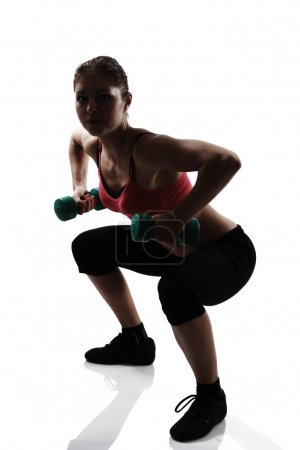 Woman doing squatting with dumbbells