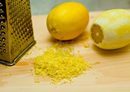 Photo pour Citrons et le zeste de citron sur une planche en bois avec râpe - image libre de droit