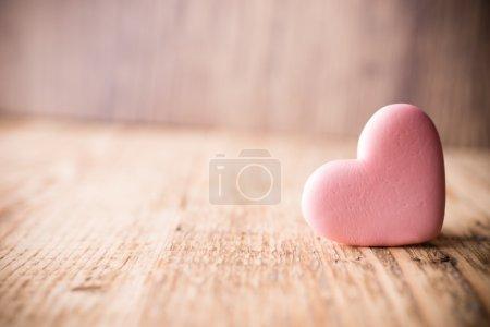 Photo pour Bonbons roses en forme de coeur sur un fond en bois . - image libre de droit