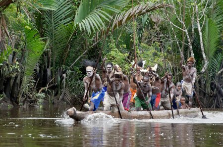 Asmat men paddling in their dugout canoe