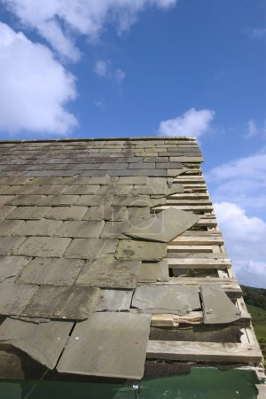 damaged roof with broken slates