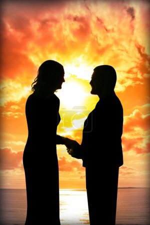 Young loving couple holding hands in silhouette