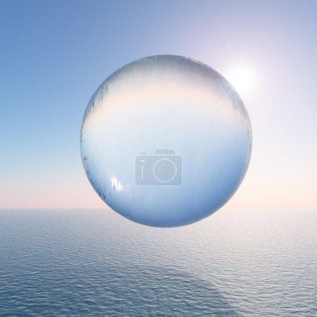 Foto de Una esfera de agua surrealista flotando sobre el mar contra un cielo despejado y el sol. - Imagen libre de derechos