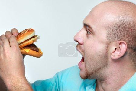 Photo for Funny man eating hamburger on grey background - Royalty Free Image