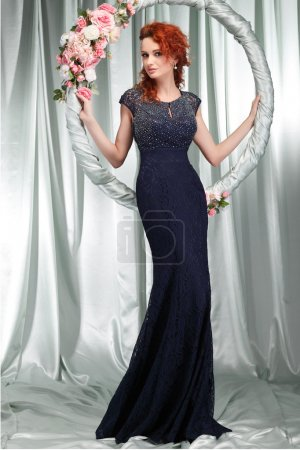 Beautiful sexual redheaded girl in evening dress with the hoop with pink flowers