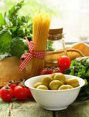 Zátiší olivy, byliny, cherry rajčátky a italské těstoviny