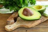 Zralé avokádo nakrájíme na polovinu na dřevěný stůl