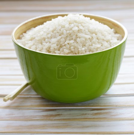 Uncooked white rice in a green bamboo bowl
