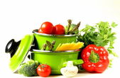 Zelené hrnce plné zeleniny (rajčata, chřest, žampiony, brokolice) a těstoviny