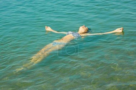 Photo pour Adolescente couchée sur la surface de l'eau de mer turquoise dans une zone côtière peu profonde - image libre de droit