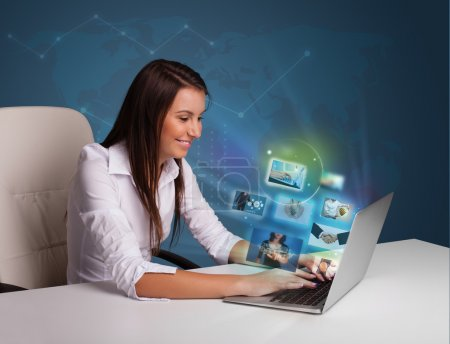 Photo for Beautiful young girl sitting at desk and watching her photo gallery on laptop - Royalty Free Image