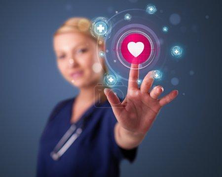 Photo pour Jeune infirmière debout et pressant type médical moderne de boutons - image libre de droit