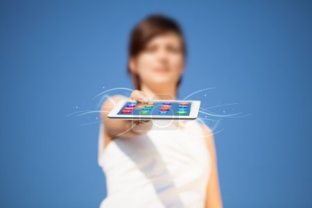 Photo for Young business woman looking at modern tablet with abstract lights and various icons - Royalty Free Image