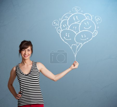 Photo for Happy young woman holding smiling balloons drawing - Royalty Free Image
