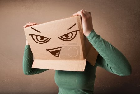 Young woman gesturing with a cardboard box on her head with evil