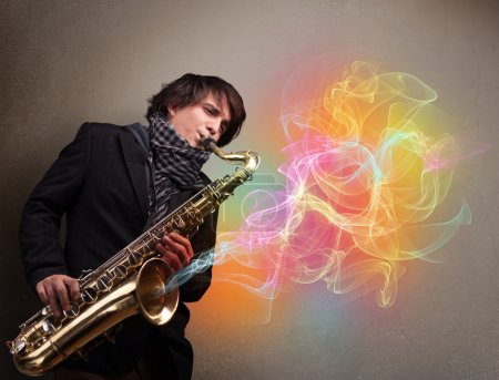 Photo for Attractive young musician playing on saxophone with colorful abstract fume comming out - Royalty Free Image