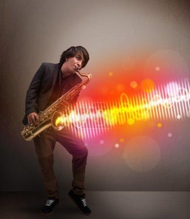 Photo pour Jeune homme attrayant jouant sur le saxophone avec des ondes sonores colorées - image libre de droit