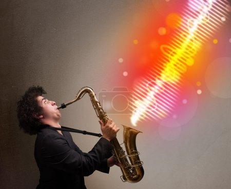 Photo pour Séduisante jeune homme jouant au saxophone avec des ondes sonores colorés - image libre de droit