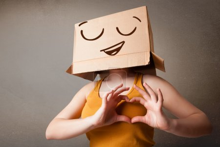 Photo for Young woman standing and gesturing with a cardboard box on her head with smiley face - Royalty Free Image