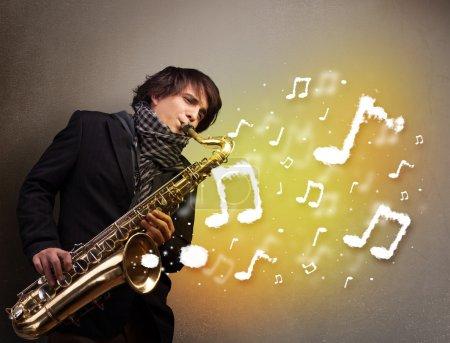 Photo pour Beau jeune musicien jouant au saxophone, avec des notes de musique - image libre de droit