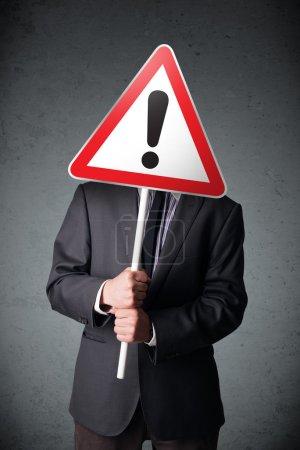 Photo pour Homme d'affaires tenant un panneau d'avertissement triangle rouge de la circulation devant sa tête - image libre de droit