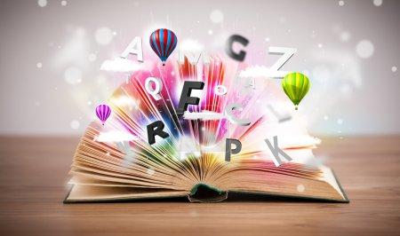 Photo pour Livre ouvert avec des lettres 3D volantes sur fond concret. Concept d'éducation colorée - image libre de droit