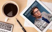 Tablet pc ukazuje časopis na obrazovce s šálkem kávy na d