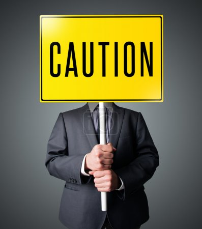Businessman holding a caution sign