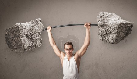 Photo for Strong muscular man lifting large rock stone weights - Royalty Free Image