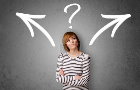 Photo for Pretty young woman making a decision with arrows and question mark above her head - Royalty Free Image