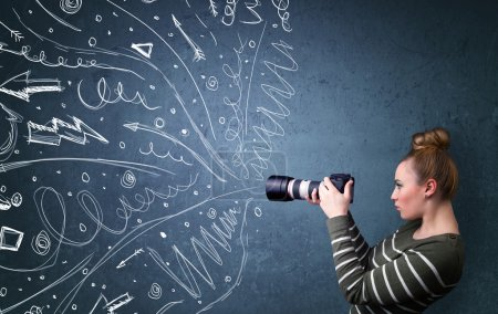 Photo pour Photographe fille tirant des images tandis que des lignes et des gribouillis dessinés à la main énergiques sortent de l'appareil photo - image libre de droit