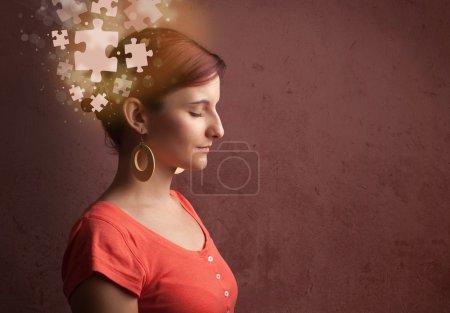 Photo pour Jeune personne pensant avec l'esprit de puzzle lumineux sur fond grungy - image libre de droit
