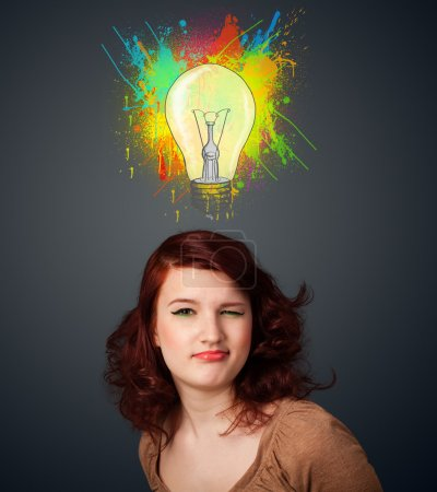 Photo for Pretty young woman gesturing with lightbulb and paint splashes above her head - Royalty Free Image