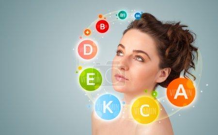 Photo pour Jolie jeune fille avec des icônes de vitamines colorées et des symboles sur fond de dégradé - image libre de droit