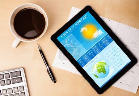 Foto de Trabajo con tablet pc mostrando la previsión del tiempo y una taza de café en un primer plano mesa de trabajo de madera - Imagen libre de derechos