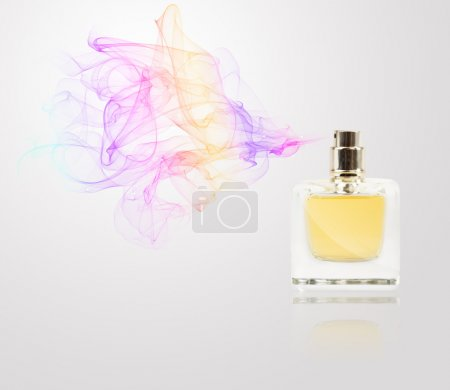 Photo for Perfume bottle spraying colorful scent - Royalty Free Image