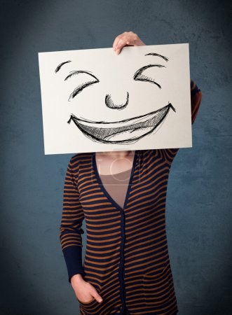 Photo for Young woman holding a paper with a drawed smiley face on it in front of her head - Royalty Free Image