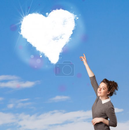 Cute girl looking at white heart cloud on blue sky