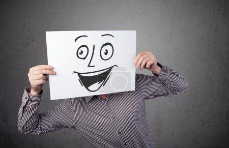 Foto de Joven hombre de negocios sosteniendo un cartón con una cara sonriente delante de su cabeza - Imagen libre de derechos