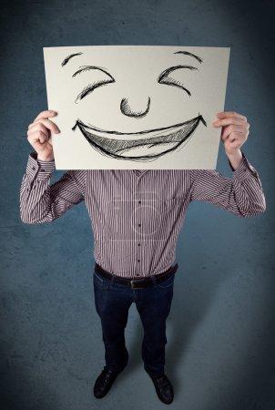 Photo pour Homme d'affaires tenant un papier avec un visage souriant dessiné devant sa tête - image libre de droit