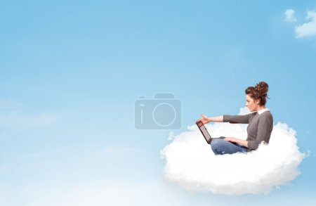 Photo for Pretty young woman with laptop sitting on cloud with empty space - Royalty Free Image
