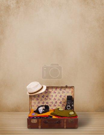 Photo pour Bagages touristiques rétro avec des vêtements colorés et copyspace sur fond grungy - image libre de droit
