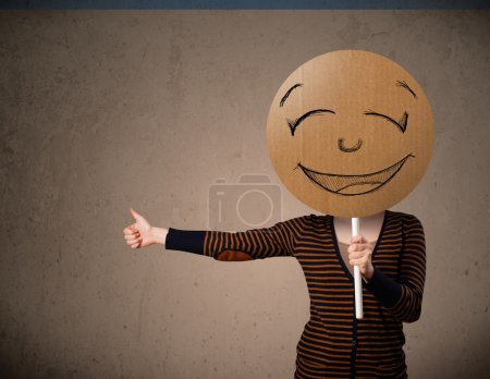 Photo for Young lady holding a cardboard smiley face emoticon in front of her head - Royalty Free Image