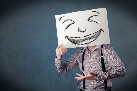 Photo for Businessman holding a paper with a drawed smiley face on it in front of his head - Royalty Free Image
