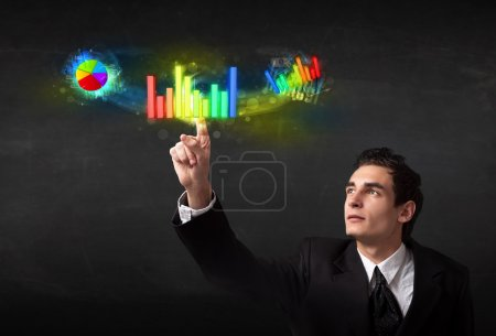 Handsome young business man touching colorful modern graph syste