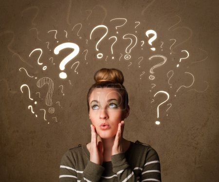 Photo for Teenage girl with question mark symbols around her head - Royalty Free Image