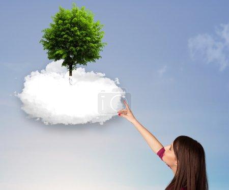 Photo pour Jeune fille pointant vers un arbre vert au sommet d'un concept de nuage blanc - image libre de droit