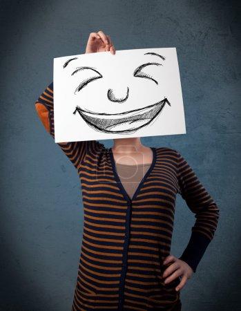 Photo pour Jeune femme tenant un papier avec un visage souriant dessiné sur elle devant sa tête - image libre de droit