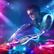 Young energetic Dj mixing music with powerful ligh...