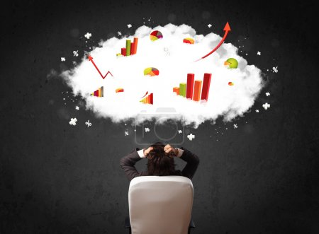 Photo for Young businessman sitting in an office chair with colorful charts in a cloud above his head - Royalty Free Image